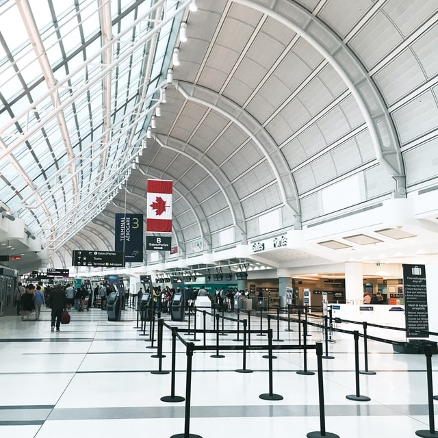 Image of Toronto Pearson Airport, indoors, a Canadian flag hangs above a nondescript group of travellers in the distance engaged in the hustle and bustle of air travel.
