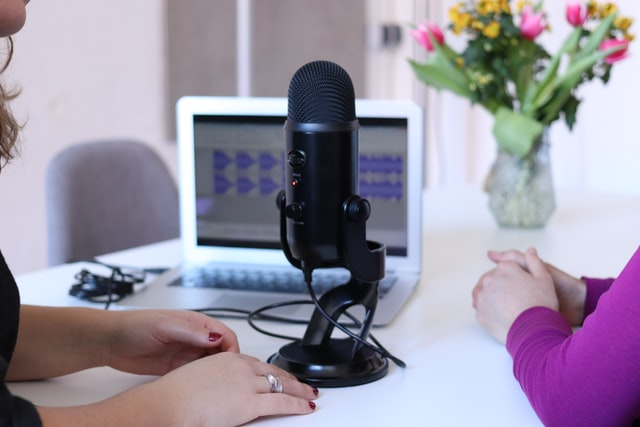 hands of two people sitting at a desk on either side of a black condenser microphone; small laptop and vase of flowers in the background